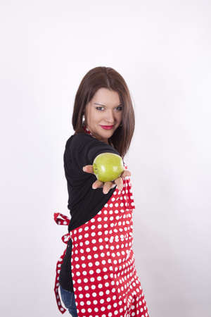 Young beautiful housewife holding and giving green apple. photo