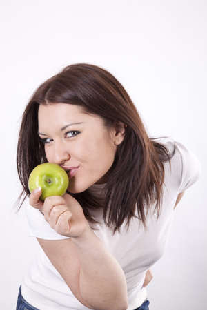sidewards: Young beautiful girl eating green apple.