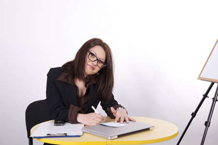 Young attractive woman at the office taking notes. photo