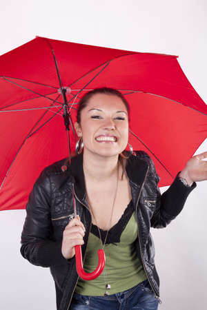 Young beautiful girl smiling under the red umbrella. photo