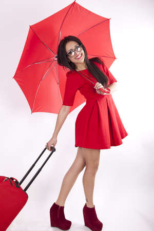 Young attractive sexy woman in red dress and with red umbrella holding luggage. Stock Photo - 13757231