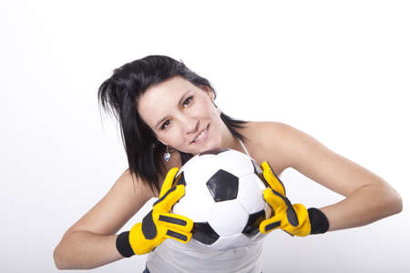 female soccer: Girl holding a football and smiling.