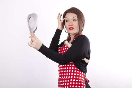 Young beautiful housewife holding rolling pin and looking at the mirror  photo