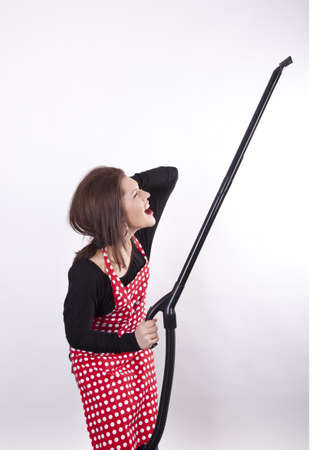 Young beautiful housewife vacuum cleaning  photo