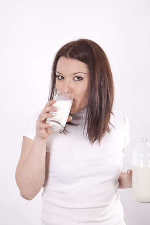 Young beautiful woman drinking milk from a glass. photo
