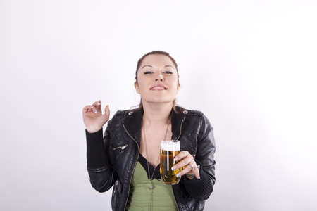 Young beautiful woman with a glass of beer and beer foam on her nose. photo