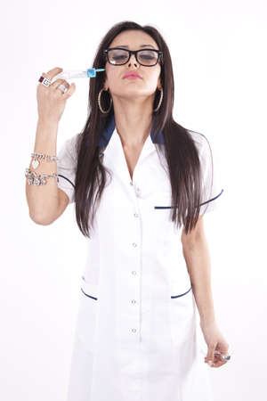 Young beautiful woman doctor with syringe next to her chin. photo