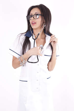 Young beautiful female doctor listening to her own heart with stethoscope. photo