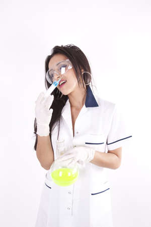 Young beautiful laboratory technician with syringe and test tube. photo