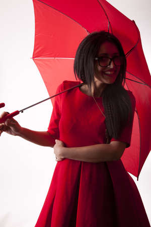 Young attractive sexy woman in red dress and with red umbrella smiling. Stock Photo - 13817038