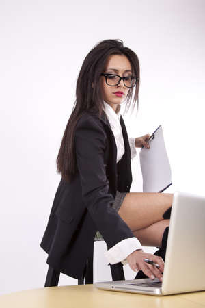secretary skirt: Young attractive sexy business woman with glasses working.