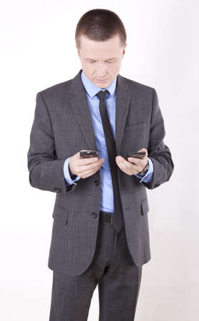Portrait of a successfull young business man looking at two phones. photo