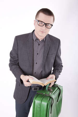 Portrait of a successfull young business man reading and holding green suitcase. photo