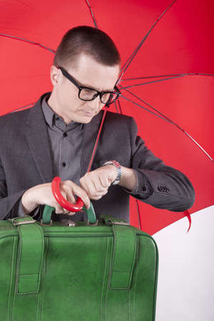 Portrait of a successfull young business man holding red umbrella  and looking at the time. photo