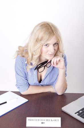 check out: Portrait of a young attractive secretary pointing at the proceed to check out.