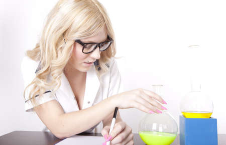 Portrait of a young attractive female laboratory technician working with test tubes. photo