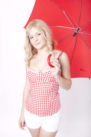 Portrait of a young attractive woman holding a red umbrella and smiling. photo
