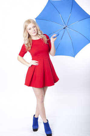 Portrait of a young attractive woman in red dress holding a blue umbrella. photo