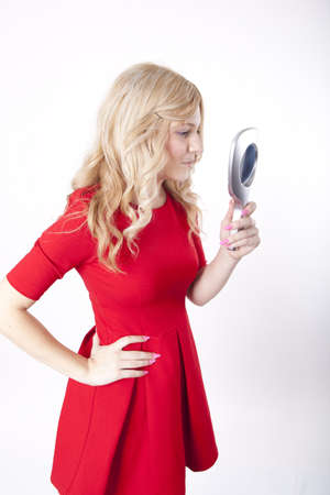 Portrait of a young attractive woman in red dress holding a mirror. photo