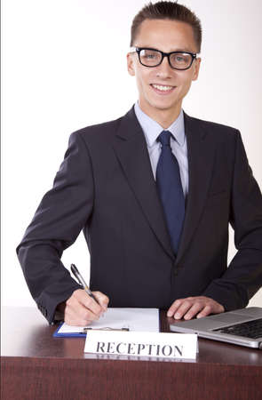 Portrait of a young attractive male receptionist smiling. photo