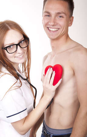 Portrait of a young beautiful female doctor checking patients heart. photo