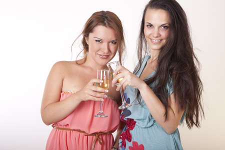 Portrait of a two young and cheerful girlfriends with colorful cocktails. photo