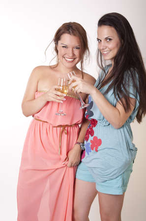 Portrait of a two young and cheerful girlfriends drinking wine. photo