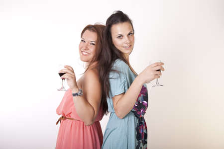 Portrait of a two young and cheerful girlfriends drinking wine.
