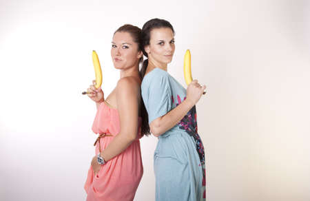 Portrait of a two young beautiful girls holding a banana as a gun. Stock Photo