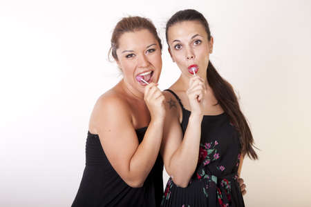 lolli: Portrait of a two young beautiful women with lollipops. Stock Photo