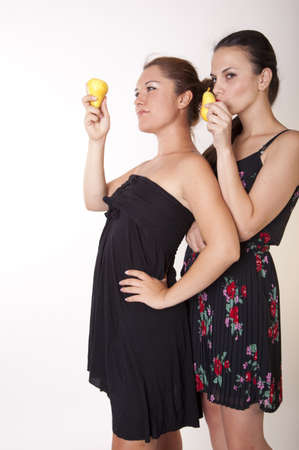 Portrait of a two young cheerful women holding pears