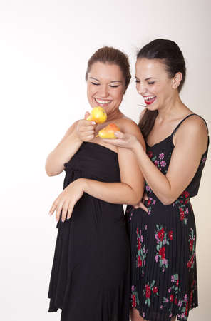 Portrait of a two young cheerful women holding pears and smiling. photo