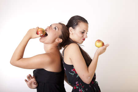 Portrait of a two sexy happy women eating apple.