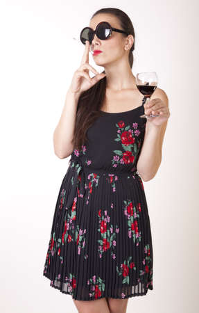 Portrait of a beautiful sexy woman smoking a cigarette and drinking wine.