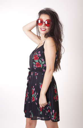 Young beautiful girl wearing funny red sunglasses.