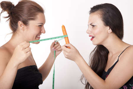 inseparable: Portrait of two attractive women with measuring tape and carrot.