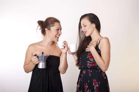 Portrait of a two beautiful sexy women drinking coffee.