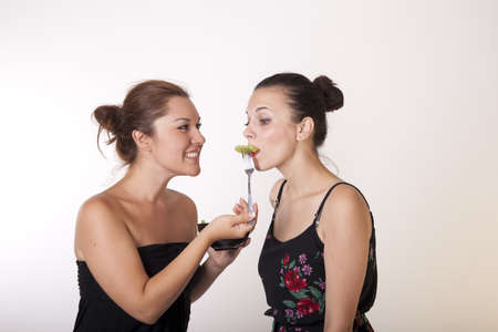 Portrait of a two sexy happy women sharing a fresh green salad.