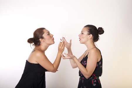 Portrait of a two beautiful sexy women blowing bubbles.