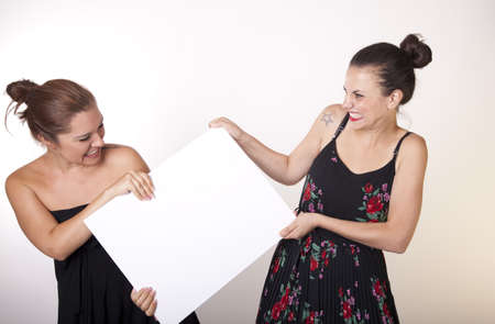 Portrait of a two beautiful sexy women holding a white board.