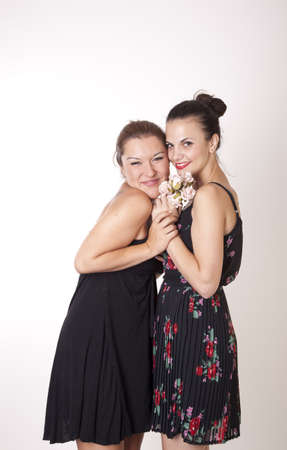 Portrait of a two beautiful sexy women sharing bouquet of flowers. Stock Photo