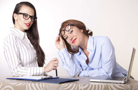 Portrait of a two young beautiful female secretaries smiling. Stock Photo - 16238379