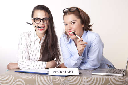 Portrait of a two young beautiful female secretaries smiling. Stock Photo - 16238330