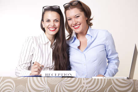 Portrait of a two young beautiful female receptionists smiling. Stock Photo - 16238350