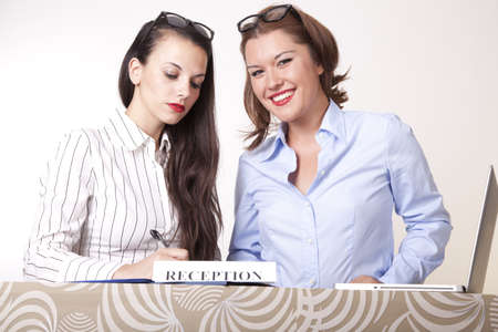 Portrait of a two young beautiful female receptionists smiling. Stock Photo - 16238336