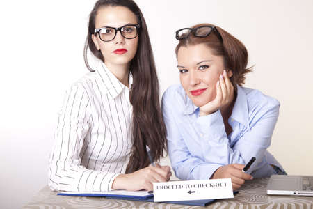 Portrait of a two young beautiful female receptionists with a sign. Stock Photo - 16238328