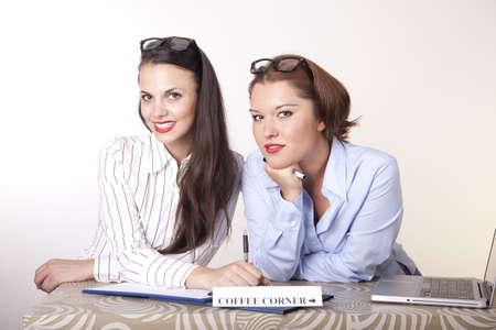 Portrait of a two young beautiful female receptionists with a sign coffee corner. Stock Photo - 16238354