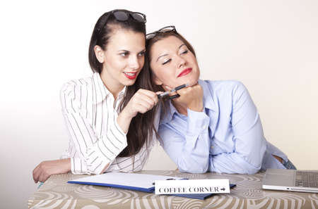 Portrait of a two young beautiful female receptionists showing direction. Stock Photo - 16238377