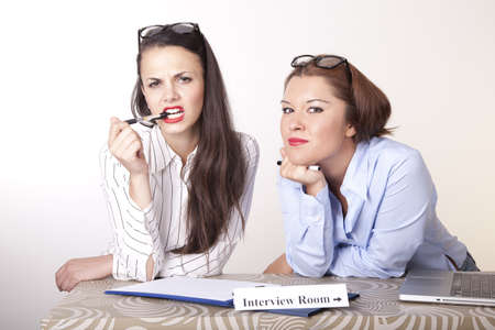 Portrait of a two young beautiful female secretaries with a sign. Stock Photo - 16238363
