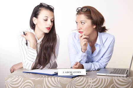 Portrait of a two young beautiful female receptionists with a sign laboratory. Stock Photo - 16238339